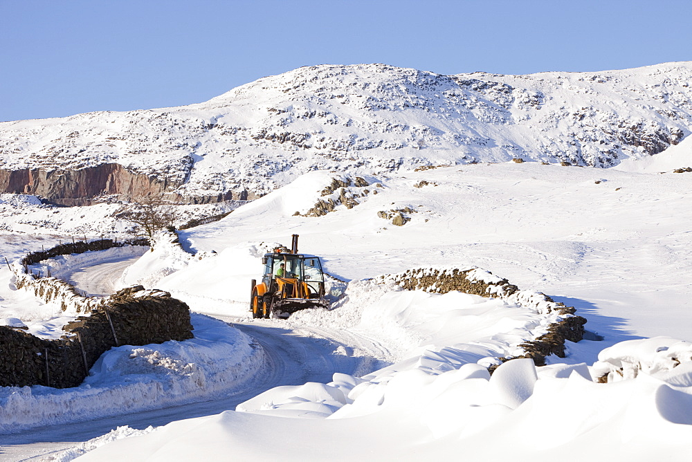 Charlie Middleton, an employee of Cumbria County Council clears snow from the blocked Kirkstone Pass, the highest mountain pass in the Lake District, Cumbria, England, United Kingdom, Europe