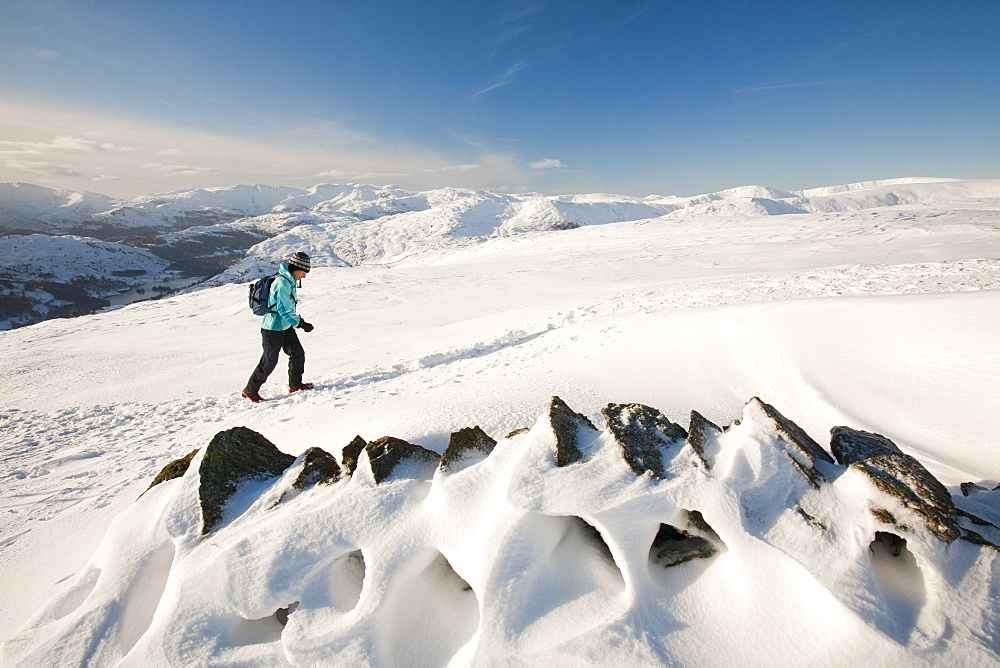 The Lake District mountains in winter snow from Red Screes, with a female hill walker, Lake District, Cumbria, England, United Kingdom, Europe
