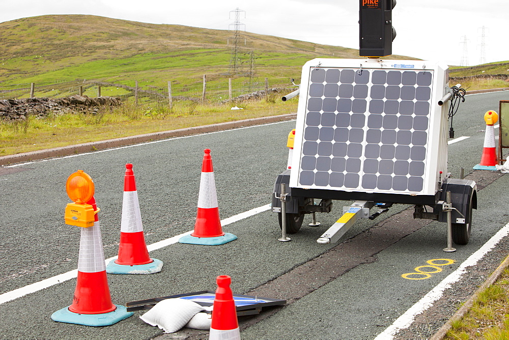 A set of traffic lights at road works, powered by a solar panel on Shap summit in the Lake District, Cumbria, England, United Kingdom, Europe - 911-6719