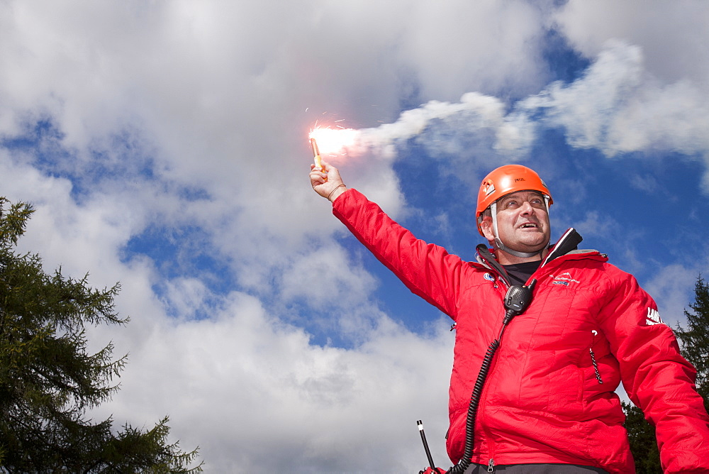 A member of Langdale/Ambleside Mountain Rescue Team uses a flare to attract an incoming Sea King helicopter to a casualty site, Grasmere, Lake District, Cumbria, England, United Kingdom, Europe
