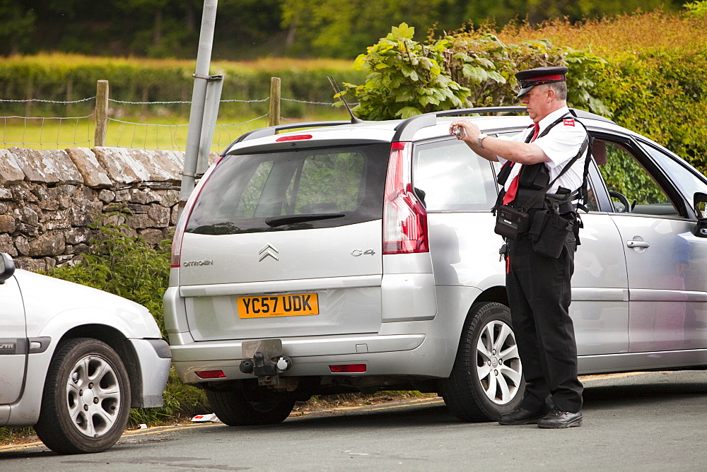 A parking attendant issues a ticket to a car parked on double yellow lines at Devils Bridge in Kirkby Lonsdale, Cumbria, England, United Kingdom, Europe
