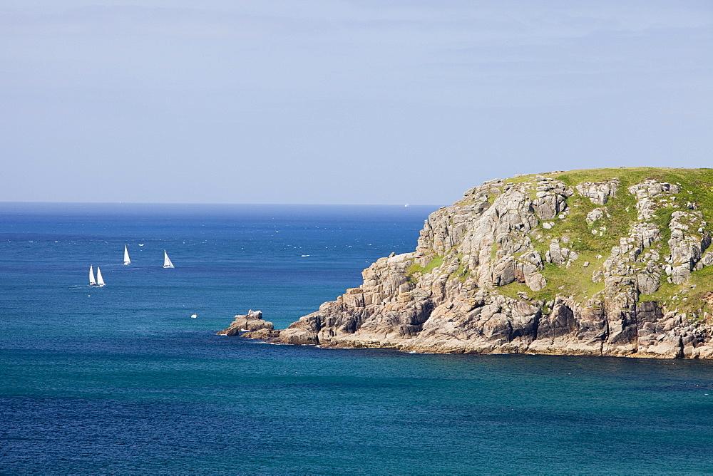 Sailing boats sailing past a headland near Lands End, Cornwall, England, United Kingdom, Europe