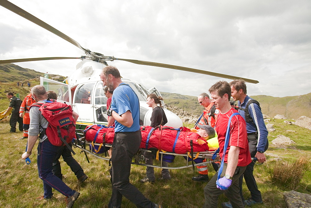 A man with a leg injury is stretchered towards an air ambulance helicopter by members of the Langdale Ambleside Mountain Rescue Team, above Grasmere, Lake District, Cumbria, England, United Kingdom, Europe