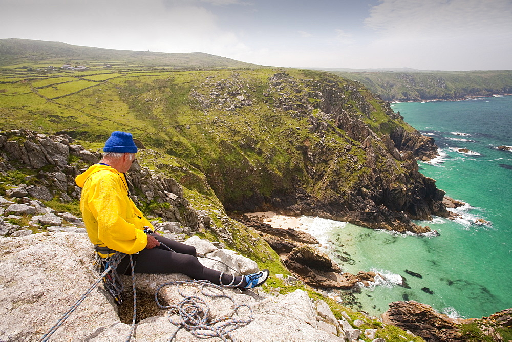 A couple in their 70s climbing on a granite sea cliff at Bosigran on the Cornish coast, Cornwall, England, United Kingdom, Europe