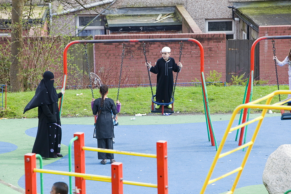 Muslims including a women in a burkha in a playground in a Muslim area of Blackburn, Lancashire, England, United Kingdom, Europe