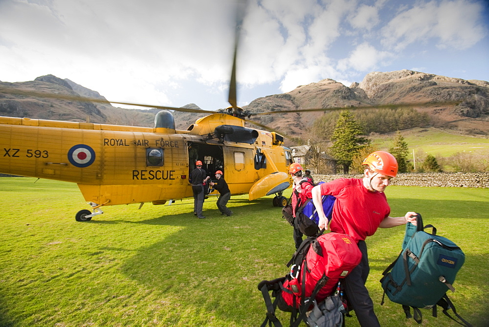 Members of Langdale Ambleside Mountain Rescue team exit an RAF Sea King helicopter during a rescue in Dungeon Ghyll in the Langdale Pikes, Lake District, Cumbria, England, United Kingdom, Europe