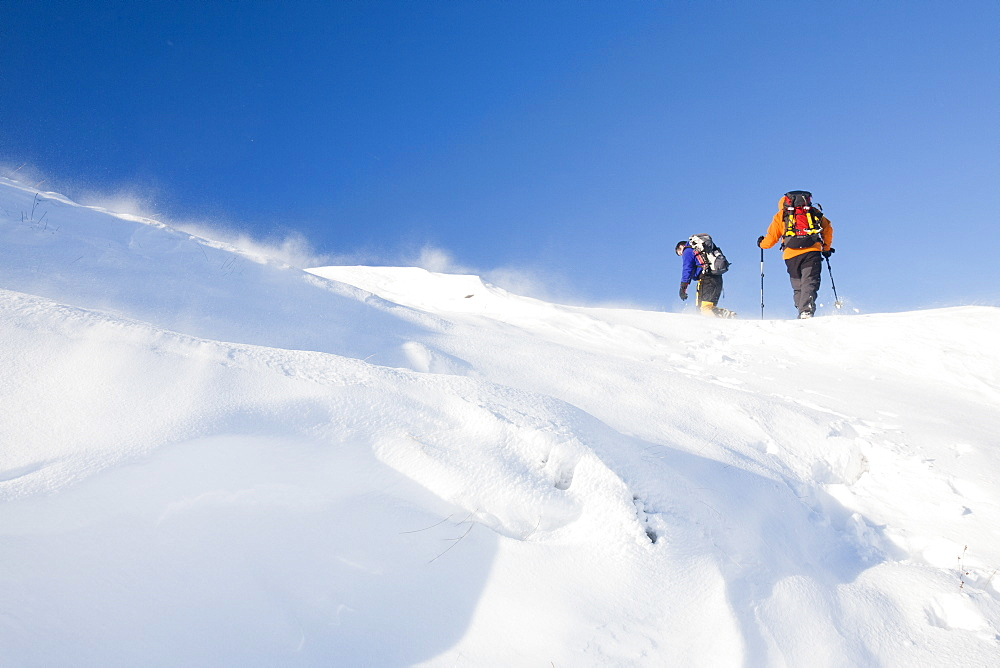 Climbers being blasted by spindrift during high winds moving snow above Grasmere in the Lake District, Cumbria, England, United Kingdom, Europe
