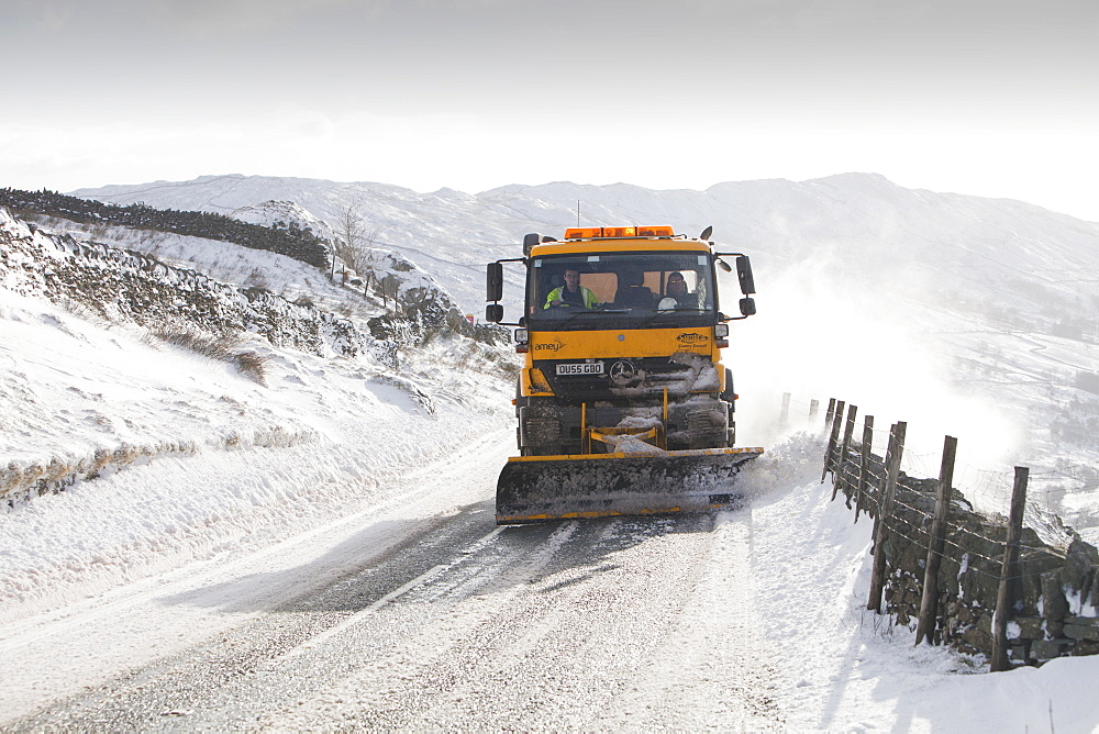 A council snow plough salting and trying to clear Kirkstone Pass in severe winter weather, November 201 Lake District, Cumbria, England, United Kingdom, Europe