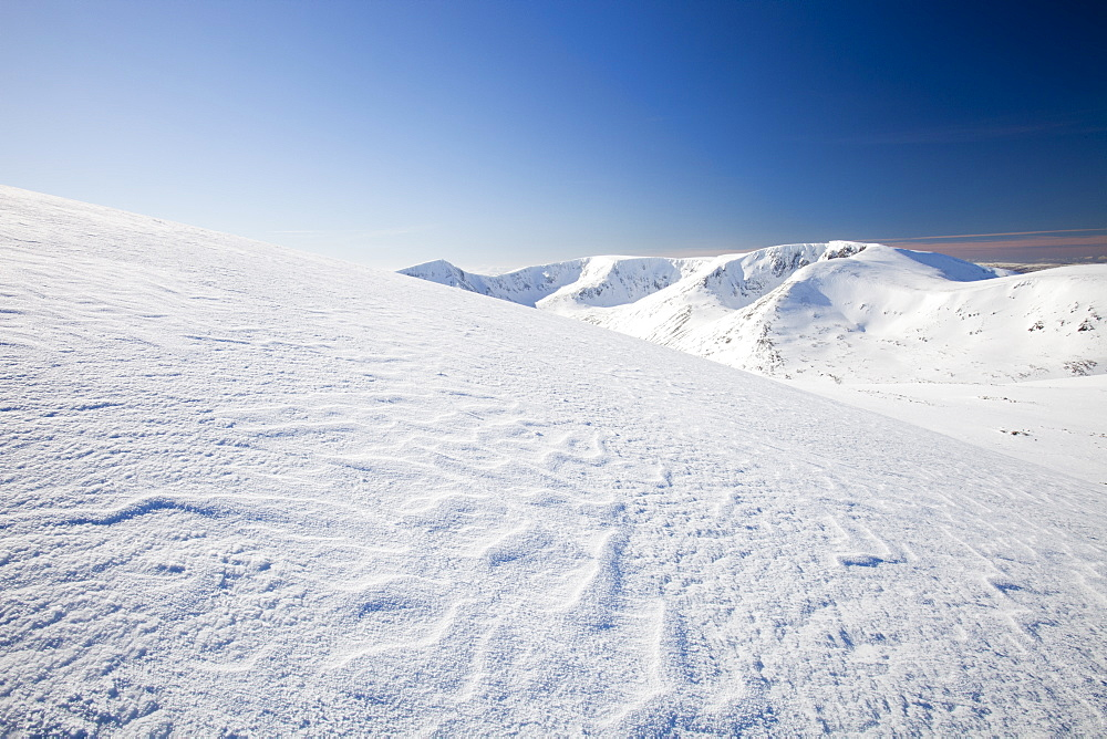 Sastrugi caused by wind drifted snow, and view towards Angels Peak and Braeriach across the Lairig Ghru from the summit of Ben Macdui in winter, Cairngorm mountains, Scotland,, United Kingdom, Europe