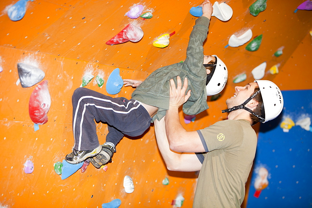 An instructor takes a young child for a lesson on the bouldering section of a climbing wall in Ambleside, Lake District, Cumbria, England, United Kingdom, Europe