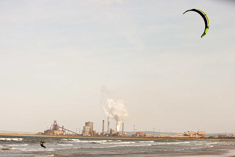 A Kite surfer in Teesmouth estuary, with the Redcar steel works behind, Teesside, England, United Kingdom, Europe