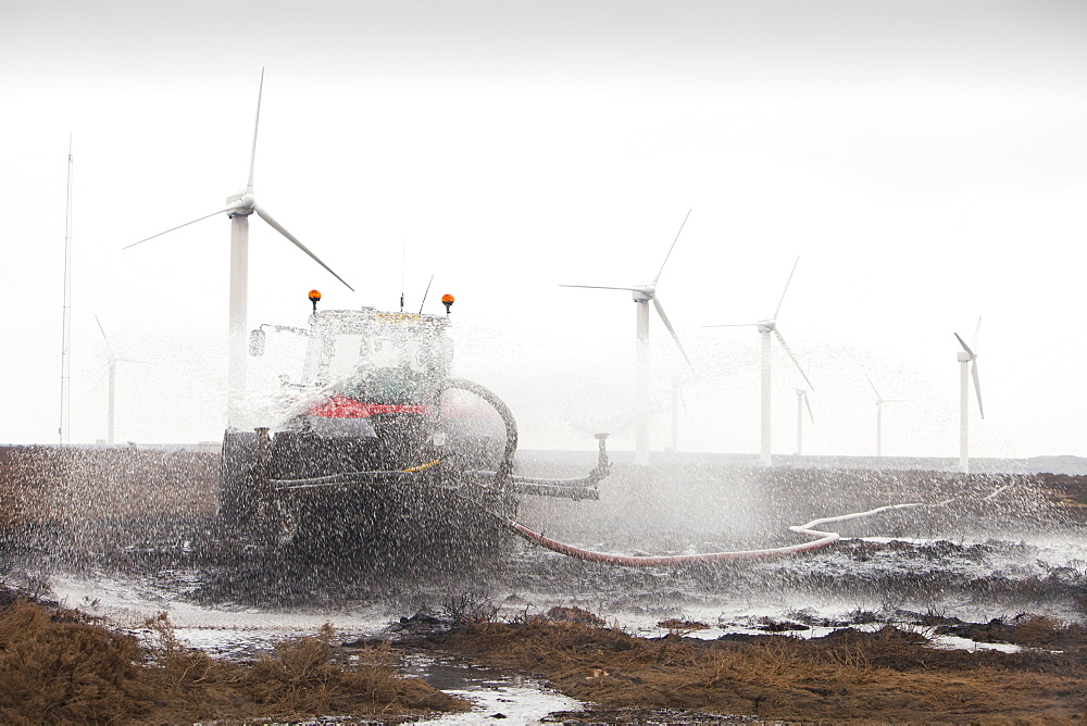 Tractors connected to hose pipes spraying the moorland to damp down the fire on Ogden Moor, near Wainstalls, above Halifax, Yorkshire, England, United Kingdom, Europe