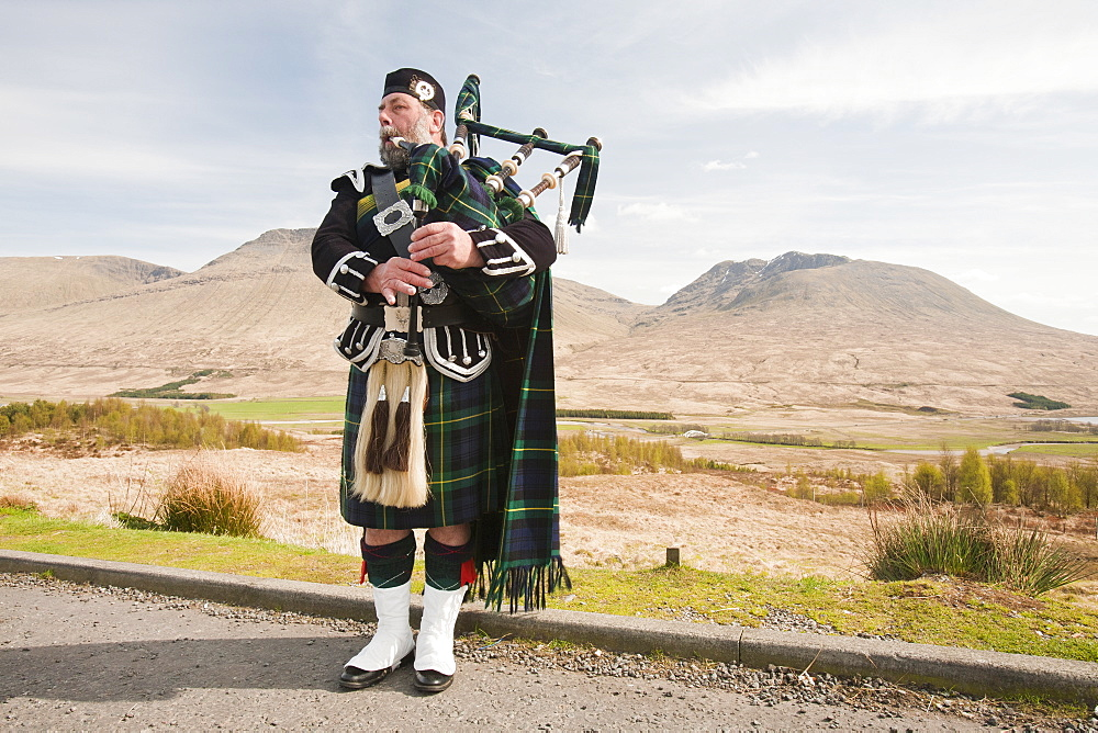 A Scottish piper in traditional dress busking on Rannoch Moor in Argyll, Scotland, United Kingdom, Europe