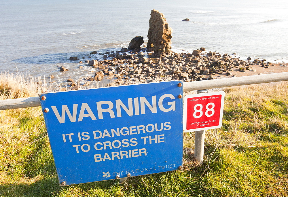 Warning sign above sea stacks on the north east coast at Whitburn, between Newcastle and Sunderland, Tyne and Wear, England, United Kingdom, Europe