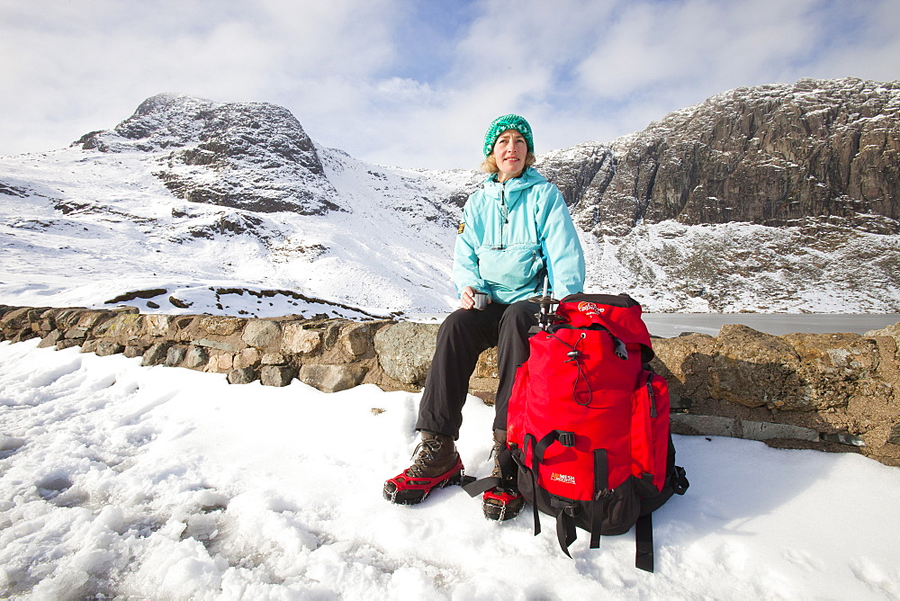 A woman hill walker by a frozen Stickle Tarn in the Langdales, Lake District, Cumbria, England, United Kingdom, Europe