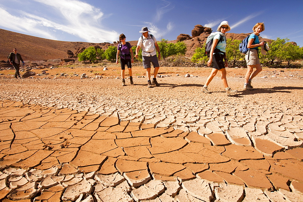 Trekkers pass a dried up river bed in the Anti Atlas mountains of Morocco, North Africa, Africa