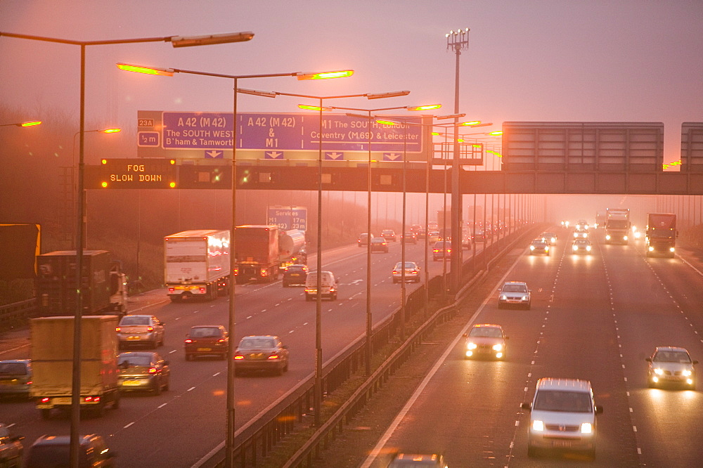Cars driving in evening fog on the M1 motorway near Loughborough, Leicestershire, England, United Kingdom, Europe