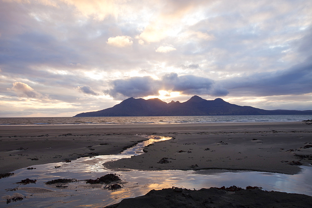 The Bay of Laig at Cleadale on the Isle of Eigg, looking towards the Isle of Rhum at sunset, Scotland, United Kingdom, Europe