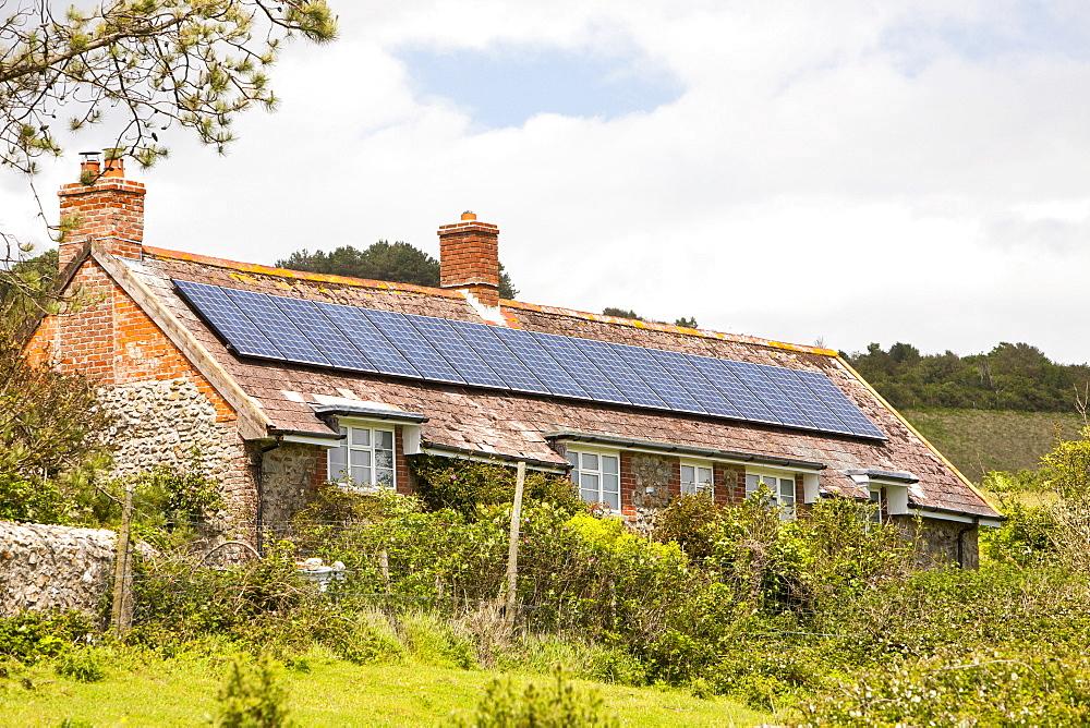 Solar panels on an old house on the Dorset coast near Charmouth, Dorset, England, United Kingdom, Europe