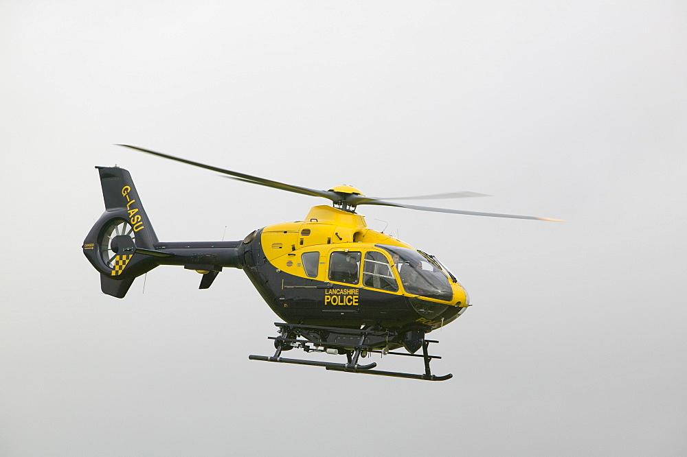A police helicopter flies over the Grayrigg train crash site near Kendal, Cumbria, England, United Kingdom, Europe