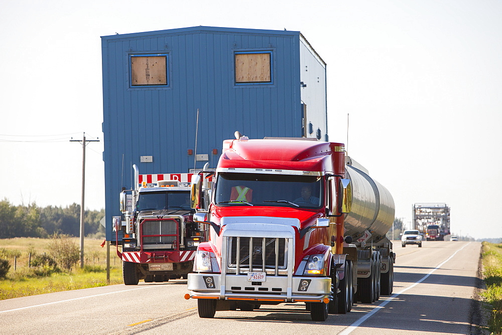 Trucks haul an oversize load of tar sands equipment for a SAGD mine, on the road towards Fort McMurray, the centre of the tar sands industry, Alberta, Canada, North America