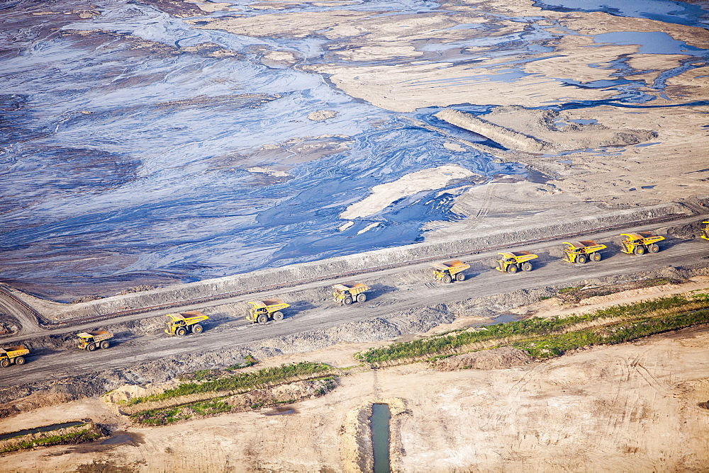 Massive dump trucks queue up to load with tar sand in a mine north of Fort McMurray, Alberta, Canada, North America