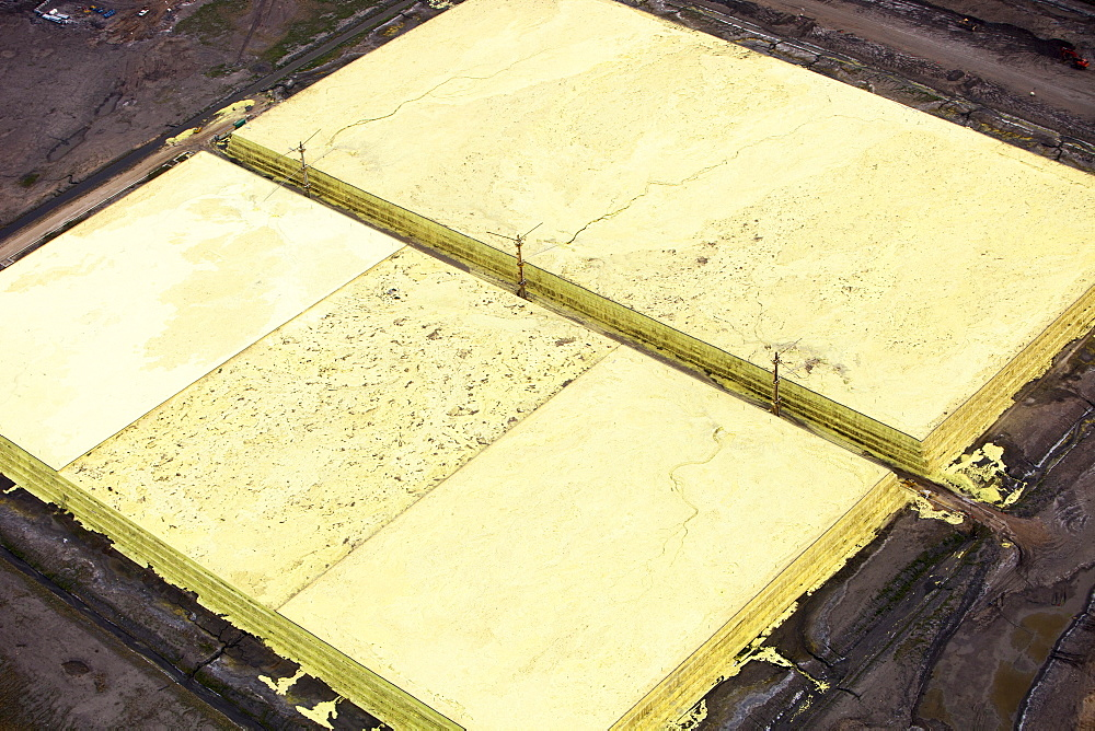 Sulphur which has to be extracted from the raw bitumen from tar sands piled up in huge mountains by the Syncrude upgrader plant near Fort McMurray, Alberta, Canada, North America