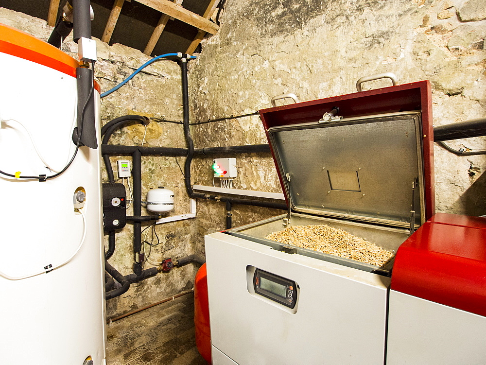 A biofuel boiler that burns wood pellets and a large hot water tank, United Kingdom, Europe