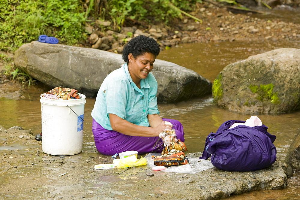 A women washing clothes in a mountain stream in Bukaya in the Fijian highlands, Fiji, Pacific