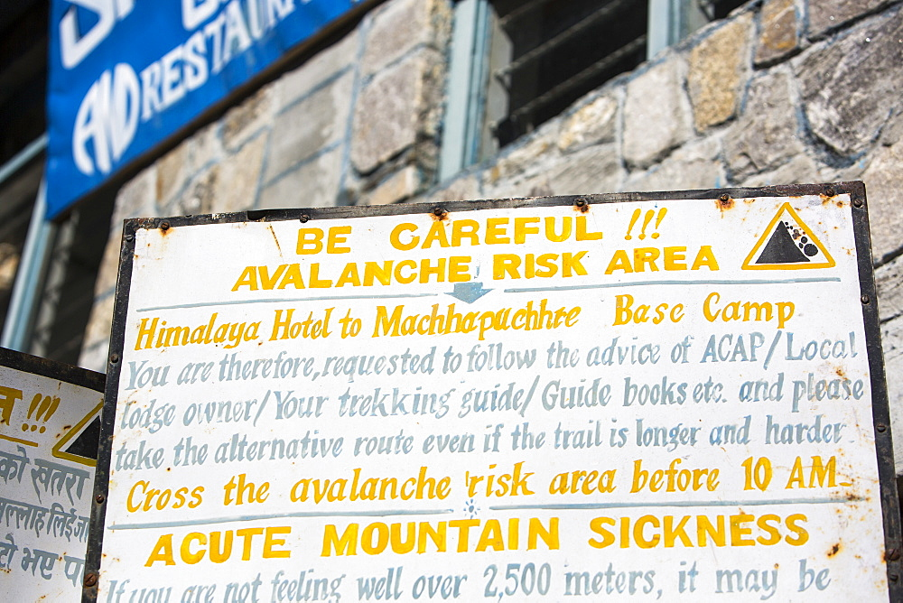 A sign about avalanche risk and acute mountain sickness in the Annapurna Sanctuary, Himalayas, Nepal, Asia