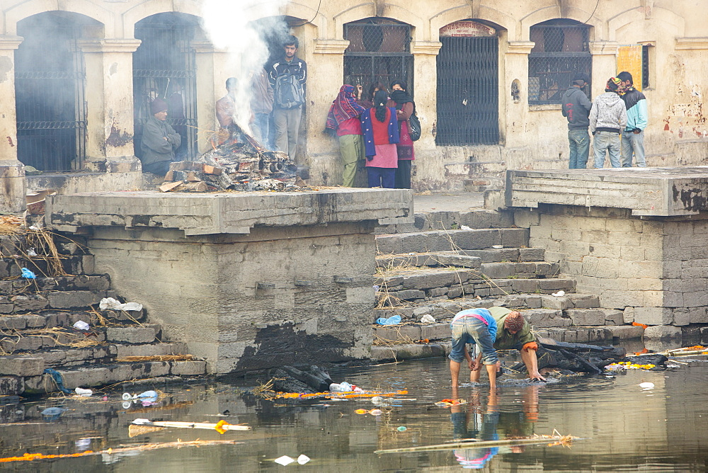 Boys panning in the Bagmati River for gold from teeth and jewellery, after the remains of funeral pyres are tipped into the river, Pashupatinath Temple, UNESCO World Heritage Site, Kathmandu, Nepal, Asia