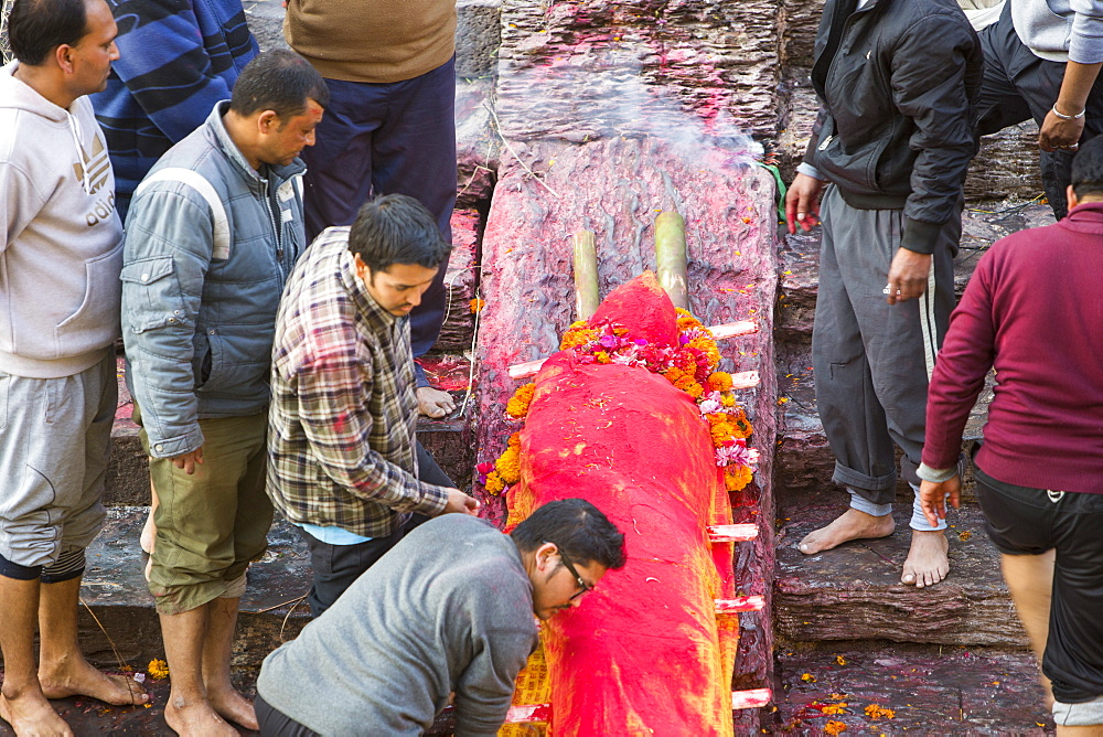 Family preparing a body for cremation at the Pashupatinath Temple, a Hindu temple of Lord Shiva located on the banks of the Bagmati River Kathmandu, Nepal, Asia