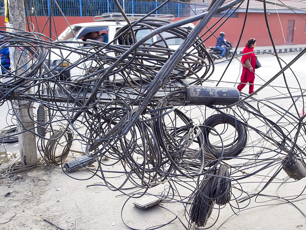 An electrician works on a tangle of electric wires in Kathmandu, Nepal, Asia