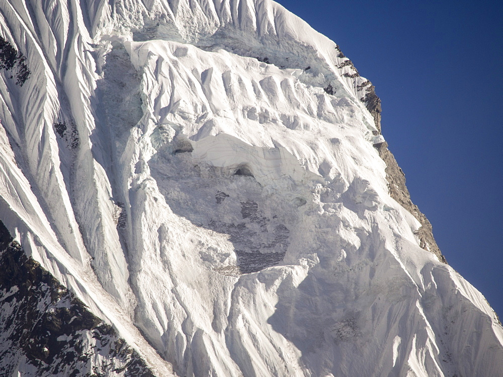 A gaping hole left where a massive block of ice detached causing an avalanche on Machapuchare (Fishtail Peak) in the Annapurna Himalaya, Nepal, Asia