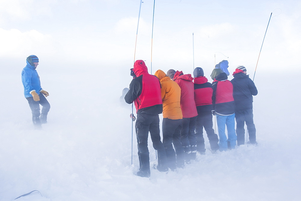 Drifting snow in Coire an Sneachda covers mountaineers training to use avalanche probes in the Cairngorm mountains, Scotland, United Kingdom, Europe