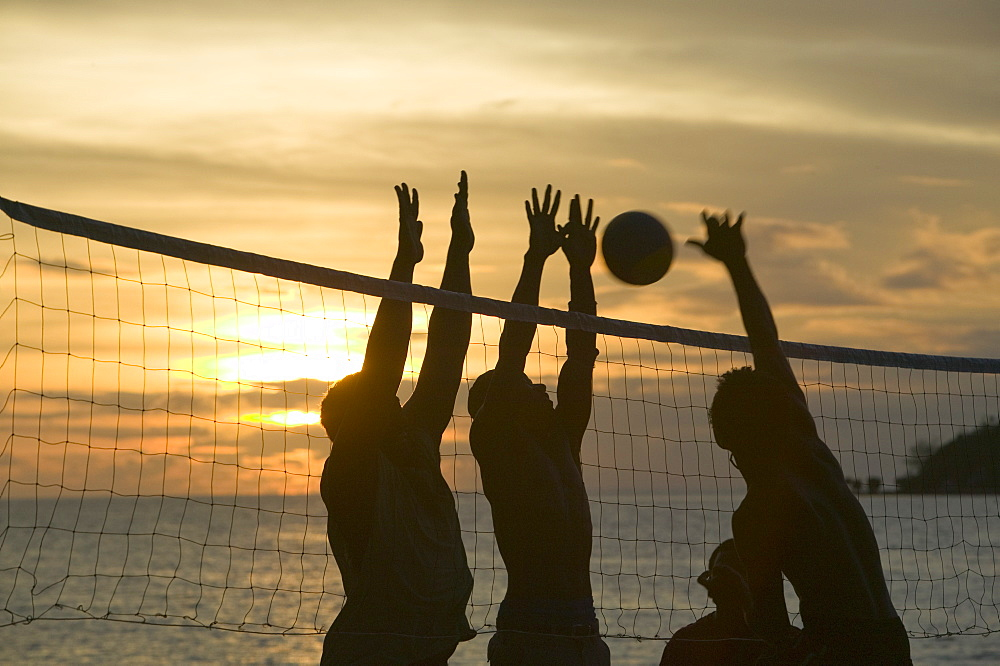 Fijian men playing beach volleyball at sunset at the Walu Beach Resort on Malolo Island off Fiji, Pacific