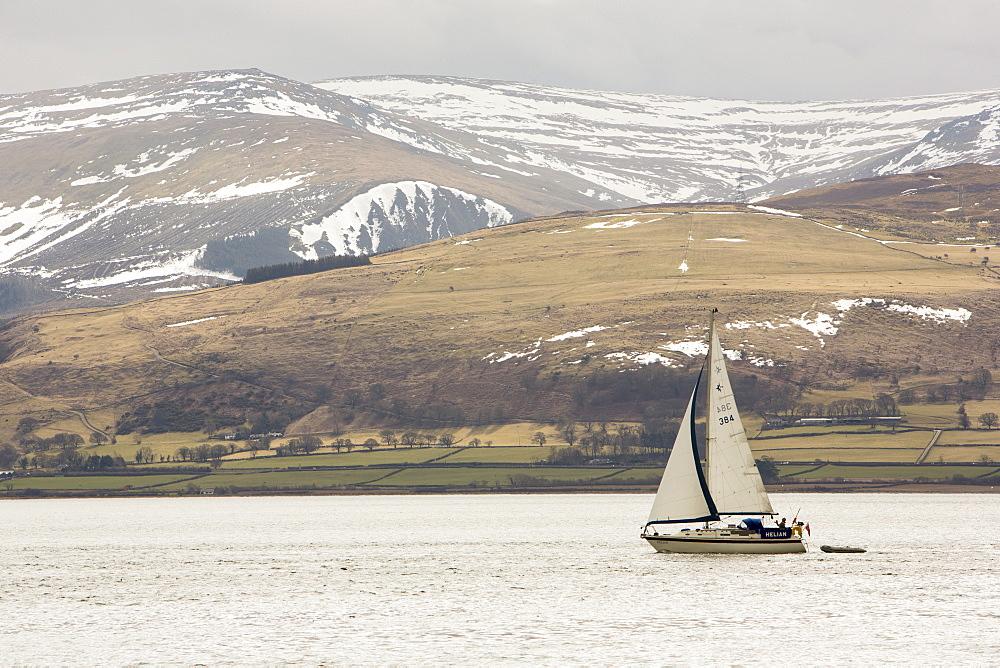 A sailing boat sailing up the Menai Straits off Beaumaris on Anglesey, Wales, United Kingdom, Europe