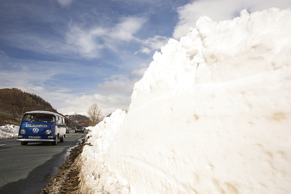 Traffic passes snowdrifts below Helvellyn during the extreme winter weather in late March 2013, Lake District, Cumbria, England, United Kingdom, Europe