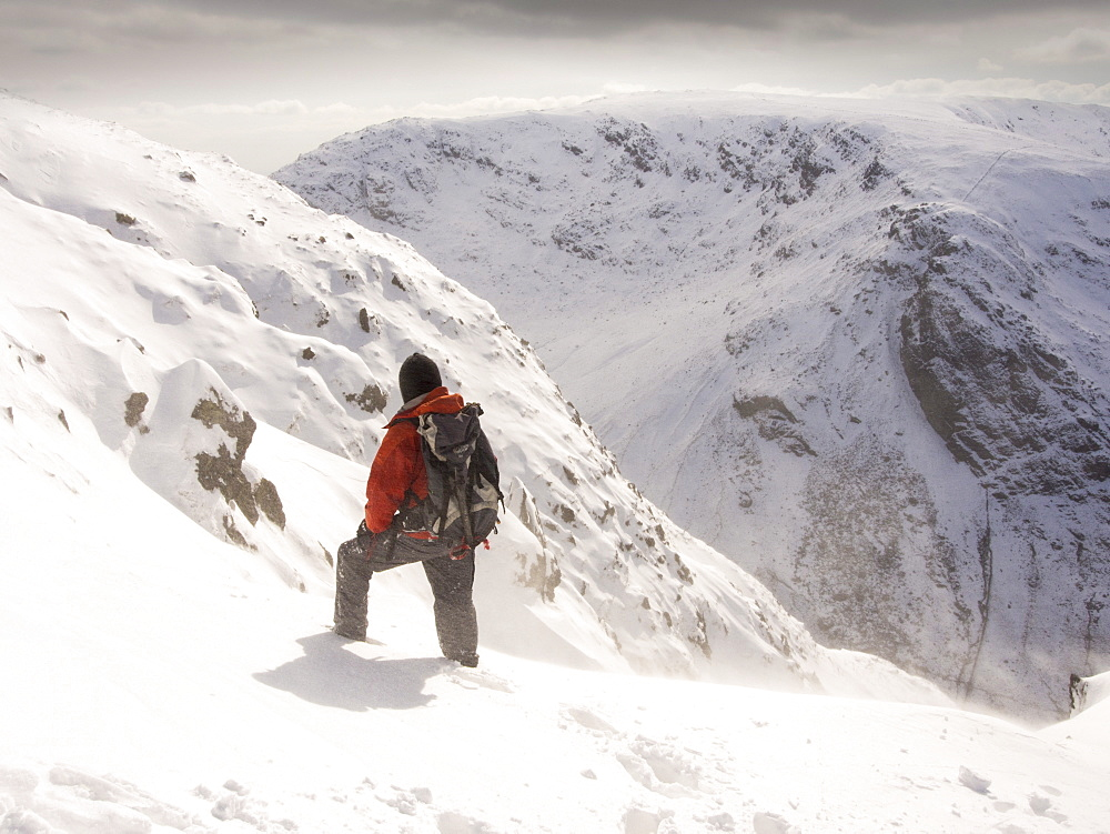 A walker on Gray Crag looking towards Stoney Cove Pike during unseasonally cold weather in late March 2013, Lake District, Cumbria, England, United Kingdom, Europe