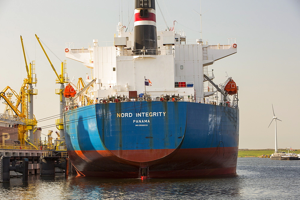 An oil tanker unloading at the docks, with a wind turbine behind, Amsterdam, Netherlands, Europe
