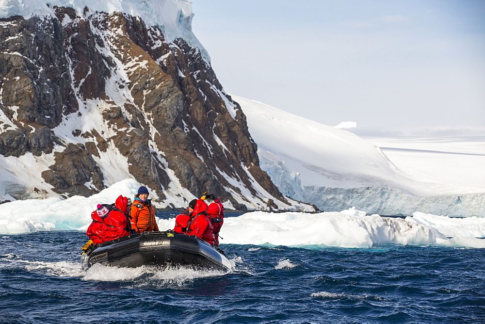 Members of an expedition cruise to Antarctica in a Zodiak off Madder Cliffs on the Antarctic Peninsular. The Antarctic Peninsular is one of the most rapidly warming areas on the planet.