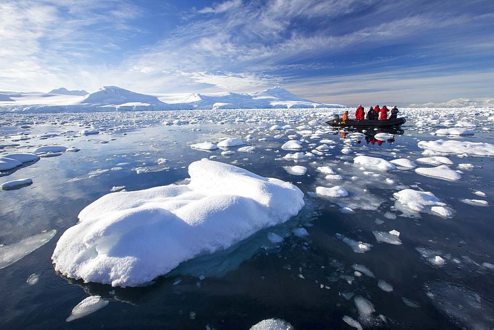 Members of an expedition cruise to Antarctica in a Zodiak in Fournier Bay in the Gerlache Strait on the Antarctic Peninsular. The Antarctic Peninsular is one of the most rapidly warming areas on the planet.