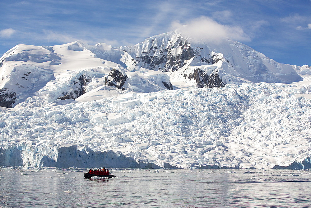 Members of an expedition cruise to Antarctica in a Zodiak in Paradise Bay beneath Mount Walker on the Antarctic Peninsular. The Antarctic Peninsular is one of the most rapidly warming areas on the planet.