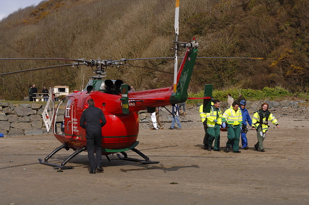 South Wales Air Ambulance helicopter and crew carrying a casualty on a stretcher at Solva harbour, Solva, Pembrokeshire, Wales, UK, Europe