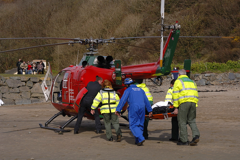 Wales Air Ambulance helicopter and crew carrying a casualty on a stretcher at Solva harbour, Solva, Pembrokeshire, Wales, UK, Europe