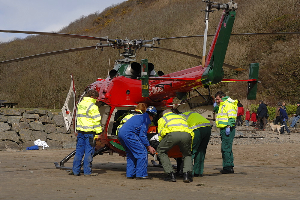 Wales Air Ambulance and crew loading a casualty into helicopter at Solva harbour, Solva, Pembrokeshire, Wales, UK, Europe
