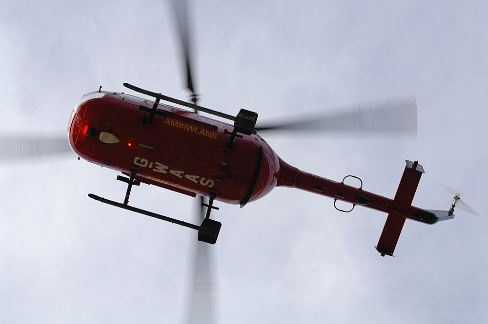 Wales Air Ambulance helicopter in flight after rescuing a casualty at Solva harbour, Solva, Pembrokeshire, Wales, UK, Europe