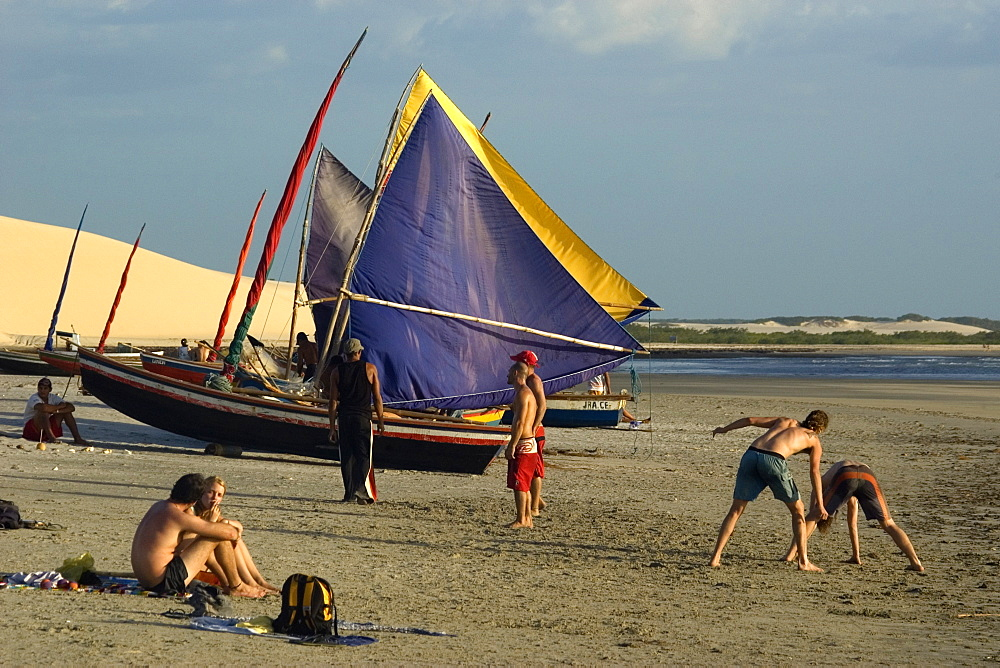 Tourists playing capoeira, traditional Brazilian martial arts and jangadas, typical Brazilian fishing boat, Jericoacoara Beach, Ceara, Brazil, South America