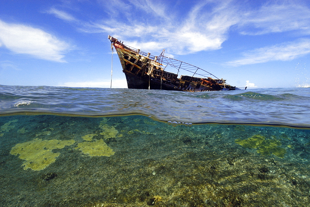 Split image of old fishing boat wreck on shallow reef, Ailuk atoll, Marshall Islands, Pacific