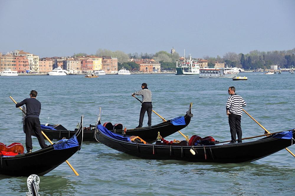 Gondoliers over Venetian lagoon, Venice, UNESCO World Heritage Site, Veneto, Italy, Europe